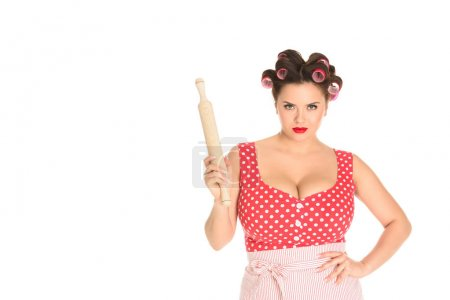 angry plus size housewife with wooden rolling pin looking at camera isolated on white