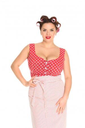 Photo pour Souriant plus taille femme au foyer en robe rouge avec des bigoudis dans les cheveux isolés sur blanc - image libre de droit