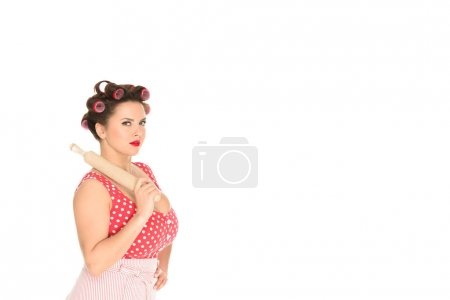 serious plus size woman with wooden rolling pin looking at camera isolated on white