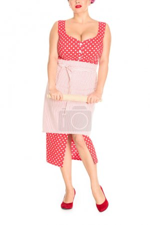 cropped shot of plus size woman in red dress with apron holding wooden rolling pin isolated on white