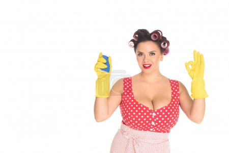 smiling plus size woman in rubber gloves with sponge showing okay gesture isolated on white