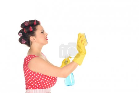 side view of plus size woman in rubber gloves with cleaning supplies wiping blank space isolated on white
