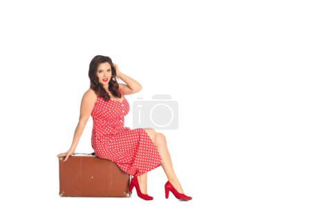 attractive plus size woman sitting on vintage suitcase isolated on white