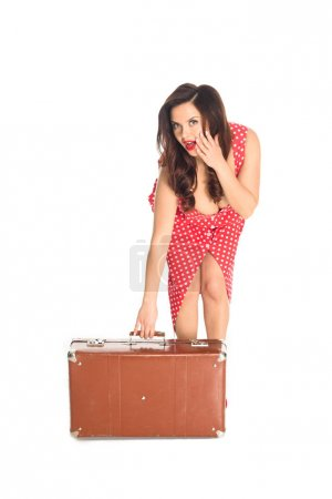 shocked plus size woman with vintage suitcase looking at camera isolated on white