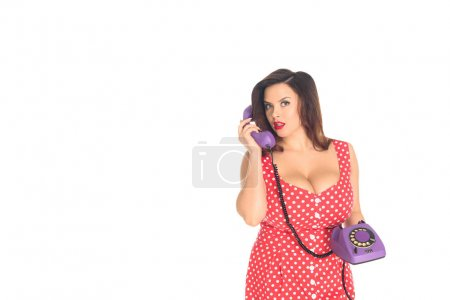 beautiful plus size woman talking by vintage rotary phone isolated on white