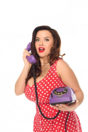 excited plus size woman talking by vintage rotary phone isolated on white