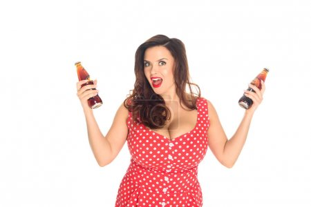 excited plus size woman with bottles of soda looking at camera isolated on white