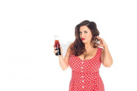 attractive plus size woman with bottle of soda looking at camera isolated on white