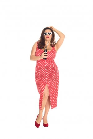 beautiful plus size woman in dress and vintage sunglasses with bottle of soda isolated on white