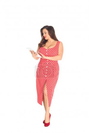 beautiful plus size woman in red dotted dress using tablet isolated on white