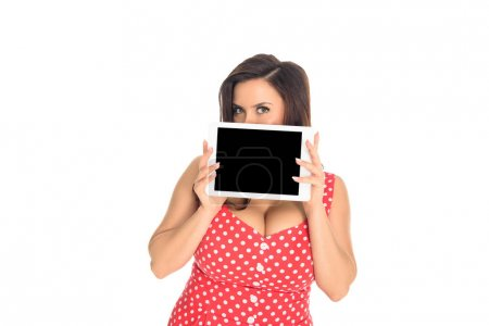 plus size woman in red dress holding tablet with blank screen in front of her face isolated on white