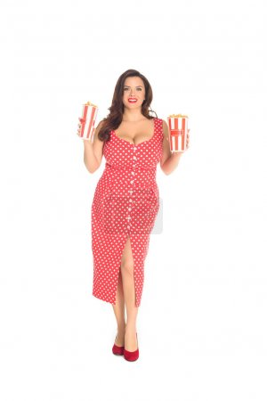 smiling plus size woman in red dress with boxes of popcorn isolated on white
