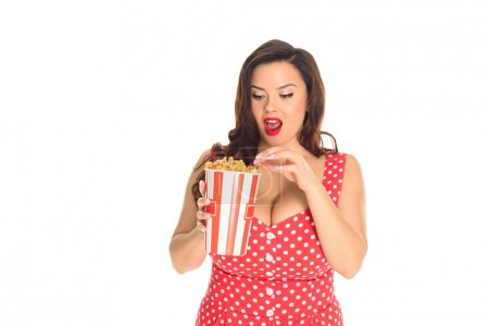 shocked plus size woman in red dress eating popcorn isolated on white