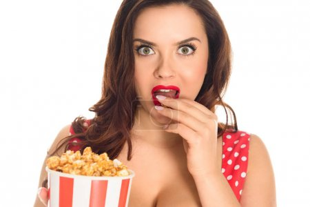 shocked plus size woman eating popcorn and looking at camera isolated on white