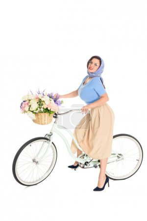 beautiful stylish pin up woman sitting on bicycle and looking at camera isolated on white