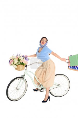 Photo for Happy pin up woman with shopping bags riding bicycle and smiling at camera - Royalty Free Image