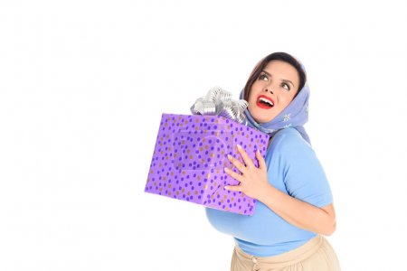surprised happy woman holding gift box and looking up isolated on white