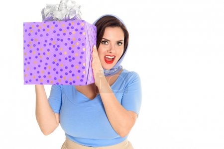 beautiful excited woman holding gift box and smiling at camera isolated on white