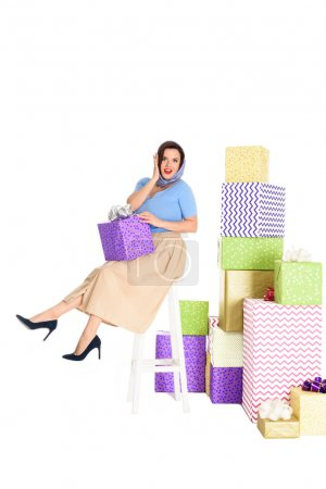 surprised pin up woman holding gift box and sitting on stool near piles of presents isolated on white