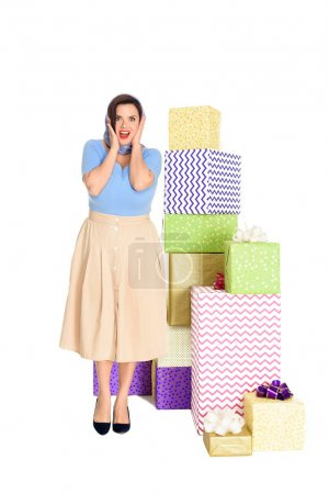 surprised stylish woman standing near gift boxes and looking at camera isolated on white