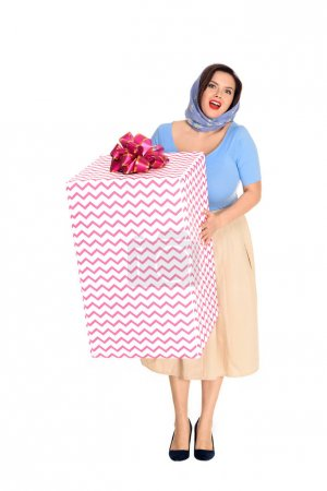 beautiful size plus pin up woman holding gift box and smiling at camera isolated on white