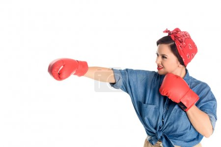 attractive size plus woman in boxing gloves hitting isolated on white