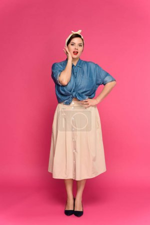 full length view of beautiful size plus pin up model looking at camera isolated on pink