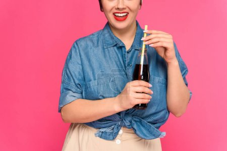 cropped shot of smiling pin up woman holding glass bottle with drinking straw isolated on pink