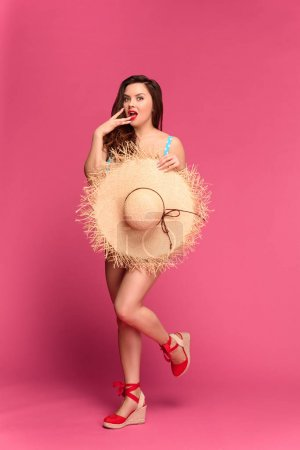 beautiful surprised woman in swimsuit holding wicker hat and looking at camera isolated on pink