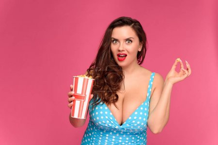 surprised young woman in swimsuit holding box of popcorn and looking at camera