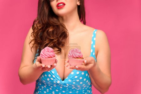 cropped shot of sexy brunette woman in swimsuit holding delicious cupcakes isolated on pink