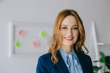 portrait of smiling businesswoman in formal wear looking at camera in office