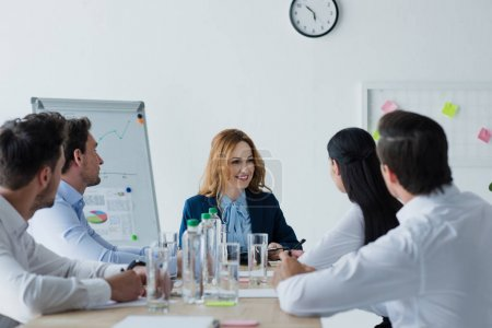 partial view of business colleagues having discussion at workplace in office