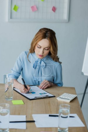 portrait of focused businesswoman doing paperwork at workplace in office