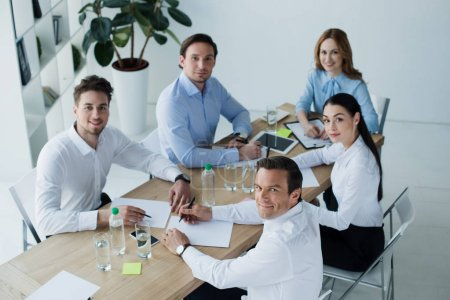 high angle view of smiling business colleagues at workplace with papers in office