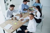 high angle view of business colleagues at workplace with papers in office