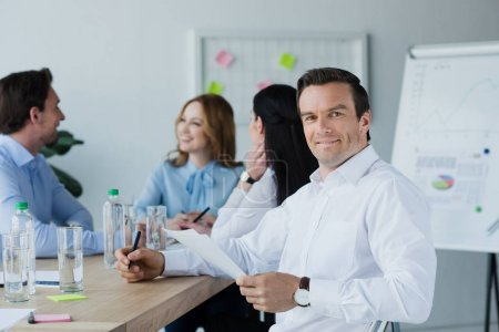 selective focus of smiling businessman with papers and colleagues at workplace in office