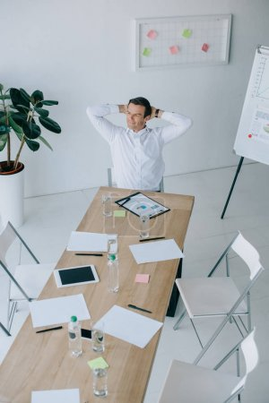 high angle view of smiling businessman in formal wear sitting alone at workplace in office
