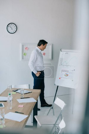 side view of businessman in formal wear looking at white board with graphic in office