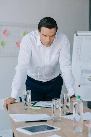 portrait of pensive businessman in formal wear at workplace in office