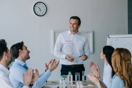 Photo for Business coworkers applauding to smiling mentor while having business training in office - Royalty Free Image