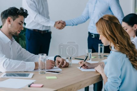 partial view of business people shaking hands while colleagues making notes at workplace in office