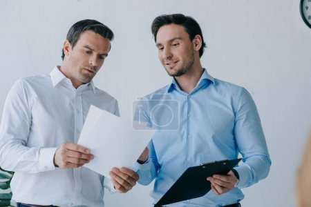 portrait of businessmen with papers discussing work in office