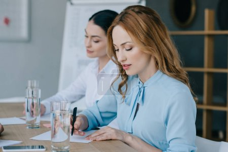 selective focus of businesswomen making notes at workplace in office