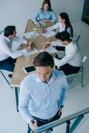 selective focus of businessman at white board and coworkers at workplace in office