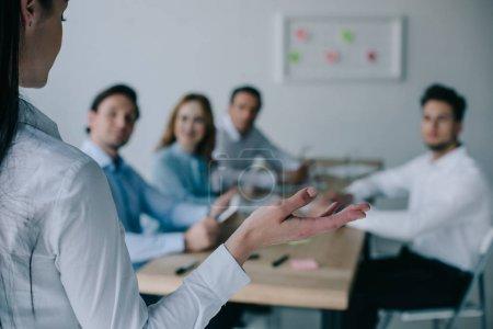 Photo pour Vue partielle de la femme d'affaires et des collègues derrière sur le lieu de travail au bureau - image libre de droit