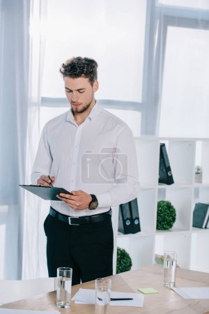 portrait of businessman in formal wear making notes in notepad in office