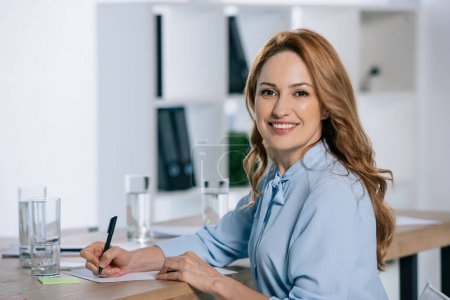 side view of smiling businesswoman looking at camera at workplace with papers in office