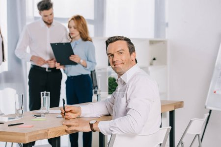 selective focus of smiling businessman at workplace and colleagues discussing work behind in office