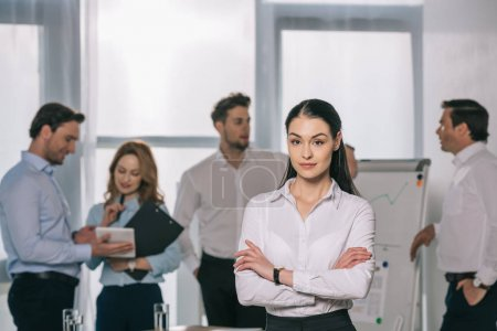 selective focus of businesswoman and colleagues behind at white board in office